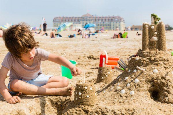Bambino e castello di sabbia sulla spiaggia di Deauville